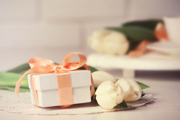 Present box and fresh tulips on wooden table closeup