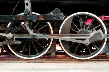 Close up wheels on steam powered locomotive.