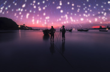 Photographer Boats at the beach during twilight stars background.