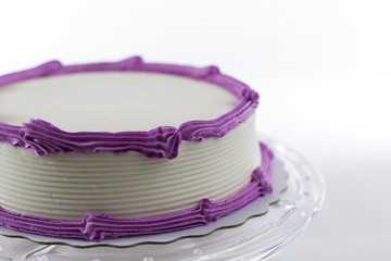 Cake with plain frosting and space for text on a bright backgrou