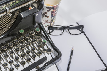 antique typewriter with coffe, a blank and a pencil on white background