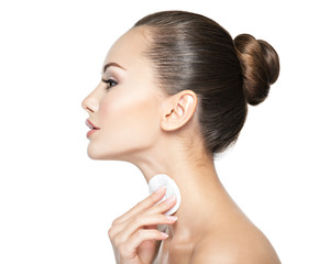 Beautiful woman cleans the neck with  cotton swab.