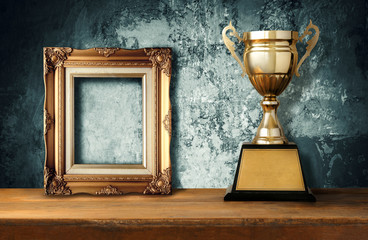 vintage frame with gold trophies on wood table