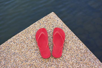 pair of red comfortable slipper placed lake side of stony floor