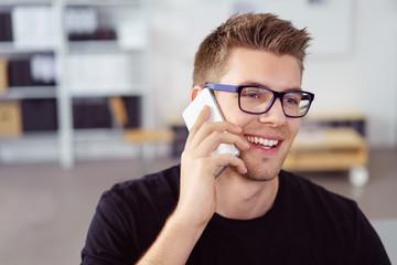 lächelnder junger mann telefoniert mit seinem handy