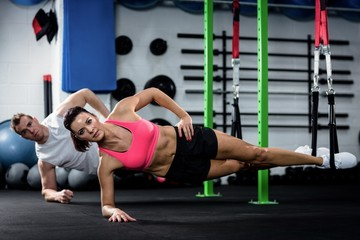 Man and woman doing suspension training with trx fitness straps