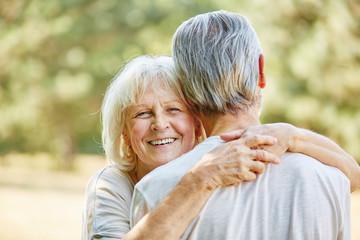 Fröhliche alte Frau umarmt Mann