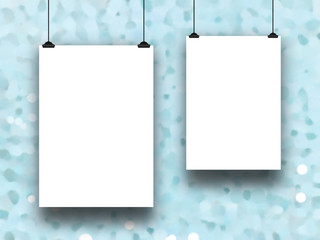 Close-up of two blank frames hanged by clips against aqua out of focus abstract background