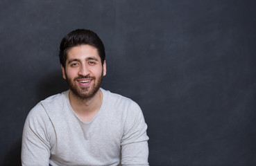 Young handsome man with great smile on the black background