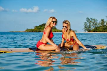 Pretty female friends having fun on a surfboard in the sea