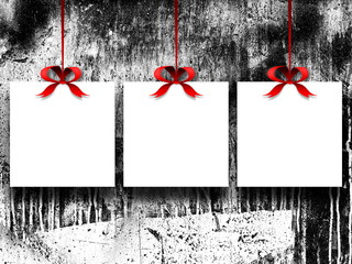 Close-up of three blank square frames hanged by red ribbons against black and white stained background