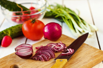 Fresh vegetables for salad: cucumbers, tomatoes, radishes and onion on wooden background. Useful healthy diet