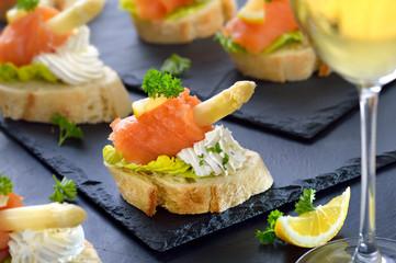 Canapes mit Lachs, weißem Spargel und Basilikum-Dill-Frischkäse, mit einem Glas Weißwein serviert - Canapes with smoked salmon, white asparagus and cream cheese with herbs, served with white wine