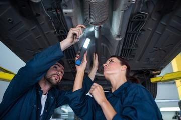 Mechanics examining car using flashlight