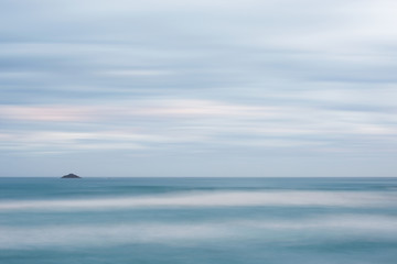 long exposure image of sea and island at dusk seen from St. Clair Beach in Dunedin, New Zealand