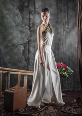 vertical full length artistic studio portrait of a woman in a white long dress with gold embroidery standing next to fallen ladder, a vintage suitcase and a bouquet of red roses on gray background