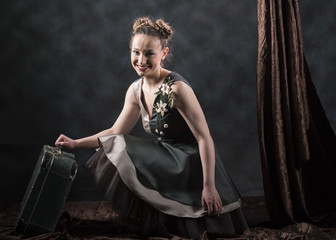 horizontal artistic studio image of a woman in a gray and green dress kneeling with a vintage suitcase in her hand and brown drapery next to her on a gray background