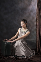vertical vintage artistic studio portrait of a female model wearing a long gray dress with handmade embroidery, kneeling next to a suitcase with brown drapery on a gray background
