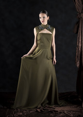 full length vertical artistic studio portrait of a young woman wearing a long green dress with neck embroidery on a gray background with brown drapery falling next to her