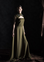 full length vertical artistic studio image of a female model wearing a long green dress with neck embroidery on a black background with brown drapery falling next to her