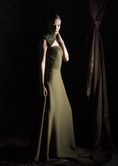 full length vertical artistic studio portrait of a fashion model wearing a long green dress with neck embroidery on a black background with brown drapery next to her