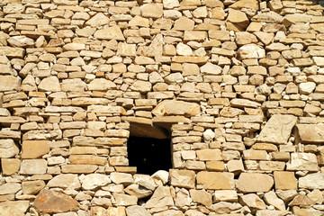 stara kamienna ściana z małym oknem