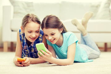 happy girls with smartphones lying on floor