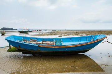 An old fishing boat moored beached on the beach at low tide.