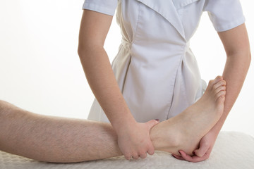 The doctor orthopedist, physical therapist examines the patient's leg