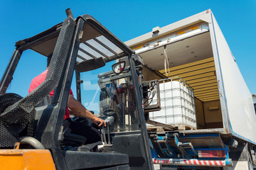 Forklift Truck Lifting White Water Tank on Pallet in Truck