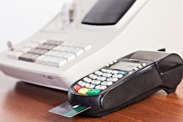 Close-up of cards servicing with POS-terminal on the cash regist