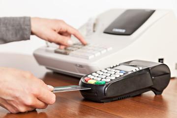 Hand push credit card Into a credit card machine. Close-up.