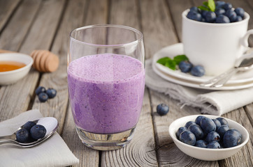 Blueberry and banana smoothie with oatmeal on the rustic wooden table, selective focus, copy space