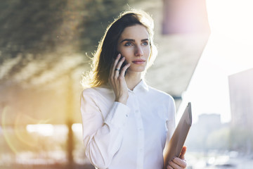 Portrait of young attractive businesswoman talking on her smartphone, close-up of smiling businesswoman in white shirt talking on mobile phone outdoors near her office, flare light