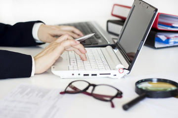 Businesswoman using laptop and calculator in the office
