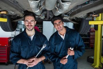 Mechanics holding work tool standing under a car