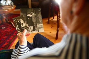 senior/ elderly woman looking at her wedding photo's