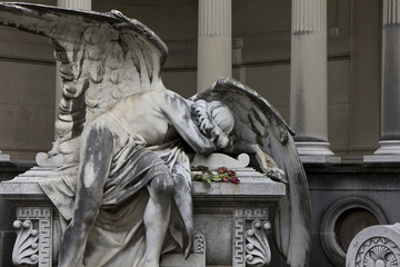 Statue of an angel  lying on a tomb  regretting the loss of a beloved one