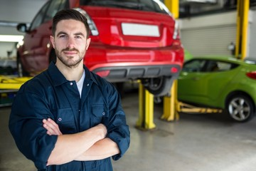 Mechanic with arms crossed smiling at camera