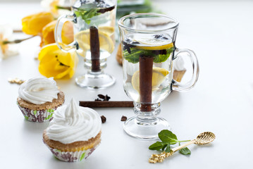 tea with lemon, cinnamon and mint in high glasses and muffins with cream on a white background, selective focus