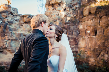 Handsome romantic groom kissing beautiful brunette bride near old wall castle