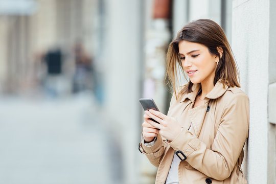 Beautiful young woman standing at the street and using her mobile phone