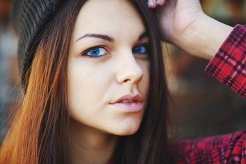 portrait of a beautiful teen girl with blue eyes wearing a red shirt and hat