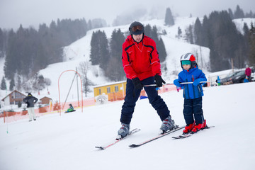 Happy little boy learning skiing with his father during winter h