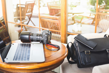 Laptop computer and dslr camera at cafe
