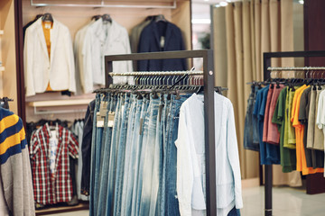 Shelves with men jeans in boutique