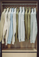 Colorful male jackets in row in a hanger