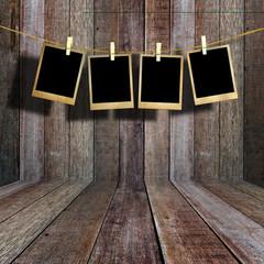Old picture frame hanging on clothesline in vintage wood room.