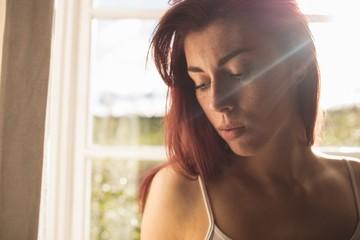 Beautiful young woman standing near window