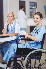 Portrait of smiling doctor sitting on wheelchair